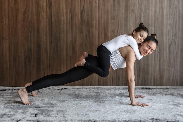 Счастливая мама и девочка вместе тренируются спортом в тренажерном зале, отжимаясь от пола