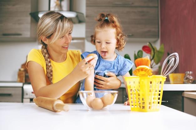 幸せなママと彼女の小さな娘が台所で料理
