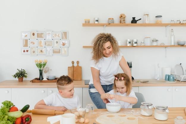 행복한 엄마와 아이들은 부엌에서 수제 케이크, 파이 또는 쿠키 반죽 재료를 혼합합니다.