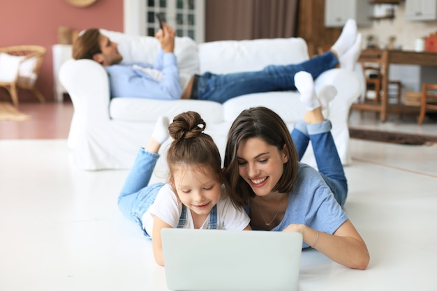 画面のラップトップを見て、ウェブカメラと話し、コンピューターアプリを介してオンラインでチャットする幸せなママと小さな子供の女の子。