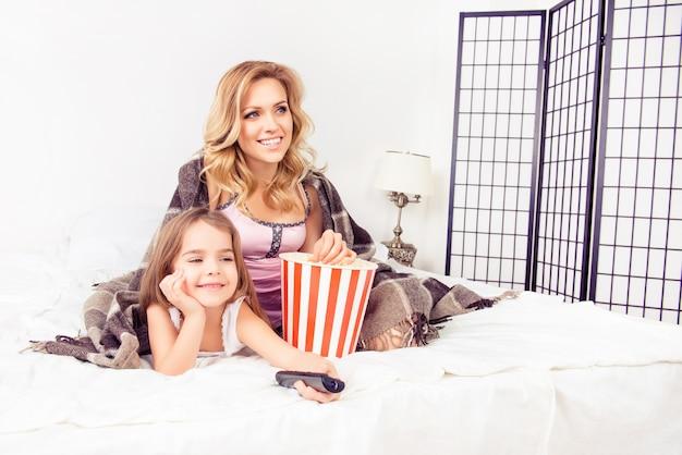 Счастливая мама и дочка смотрят телевизор с попкорном
