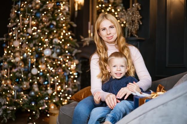 幸せなママと息子は、飾られたお祝いのクリスマスツリーを背景にソファに座っています
