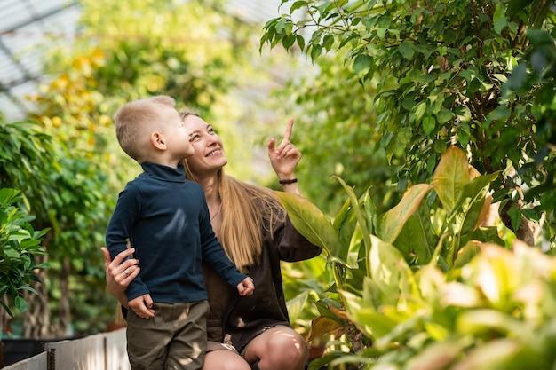 행복한 엄마와 아들은 온실에서 식물을 봅니다.