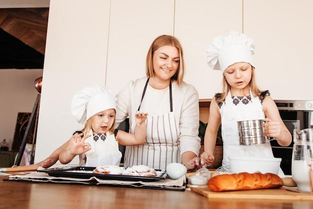 행복한 엄마와 함께 부엌에 서있는 두 딸이 빵집 만드는 법을 배우고 준비합니다. 가족 관계에 대한 아이디어.