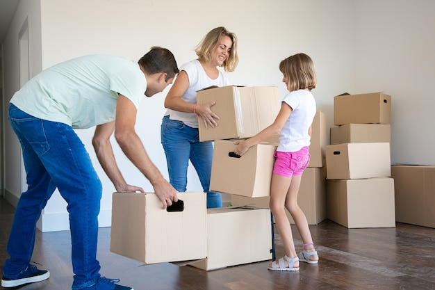 Happy mom, dad and kid holding cardboard boxes and moving to new house or apartment