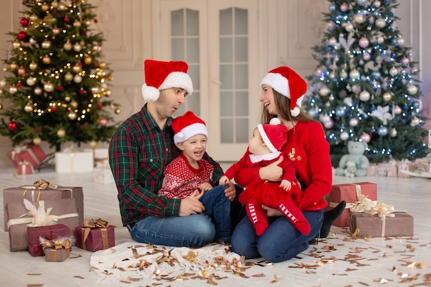 Happy mom dad and little daughter and son on santa claus hat