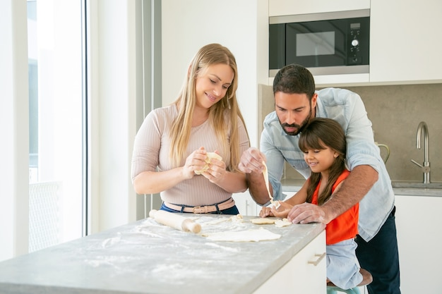 Happy mom and dad teaching daughter to knead dough at kitchen table with flour powder.