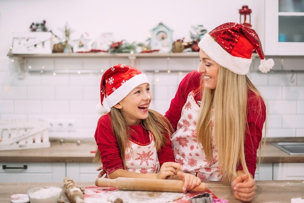 Happy mom and daughter are standing in the kitchen in red sweaters and santa hats, looking at each other.
