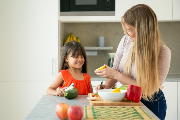 Happy mom and daughter cooking salad with lemon dressing. girl and her mother peeling and cutting vegetables on kitchen counter, chatting and having fun. family cooking or healthy eating concept