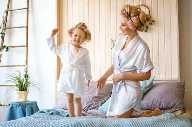 Happy mom and daughter having fun on the bed in dressing gowns