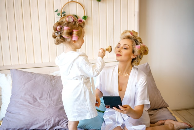 Happy mom and daughter make a make-up sitting on the bed in the bedroom