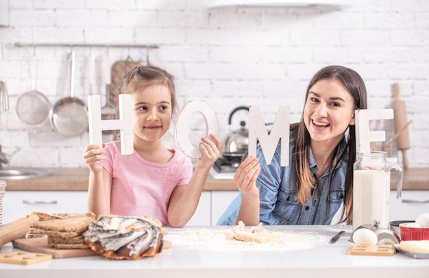 Happy mom and daughter posing with decorative word home on light kitchen.