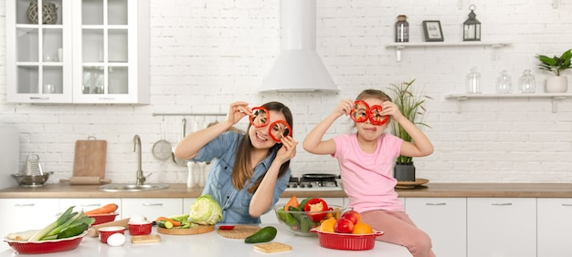 Happy mom and daughter posing with pepper rings while cooking salad.