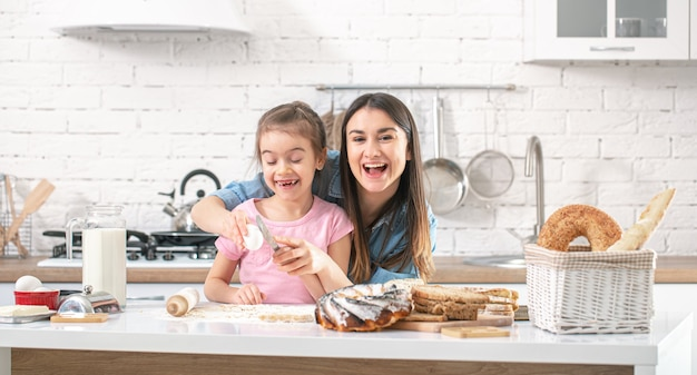 Happy mom and daughter prepare homemade cakes in a bright kitchen.