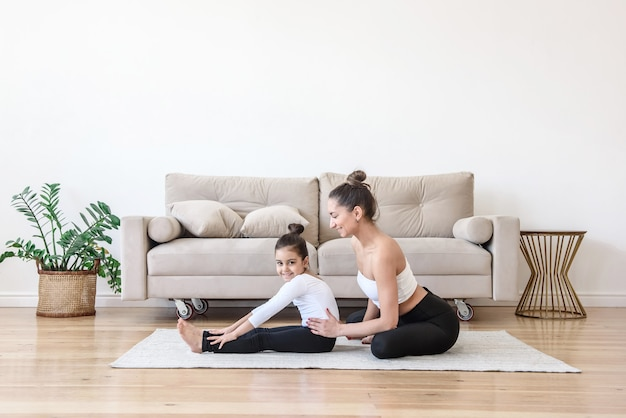 Happy mom and daughter do stretching gymnastics together at home