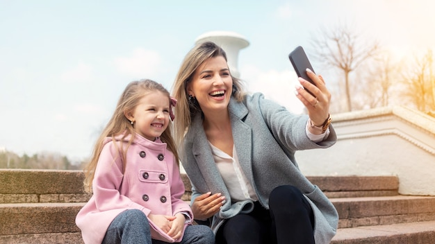 Happy mom and daughter taking selfie outdoors