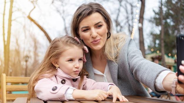 Mamma felice e figlia che prendono selfie all'aperto