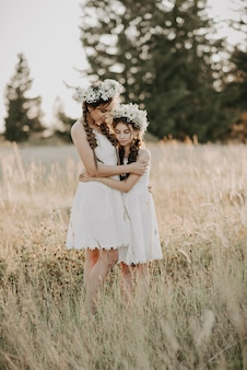 Happy mom and daughter in white dresses with floral wreaths and boho style braids in summer in a field