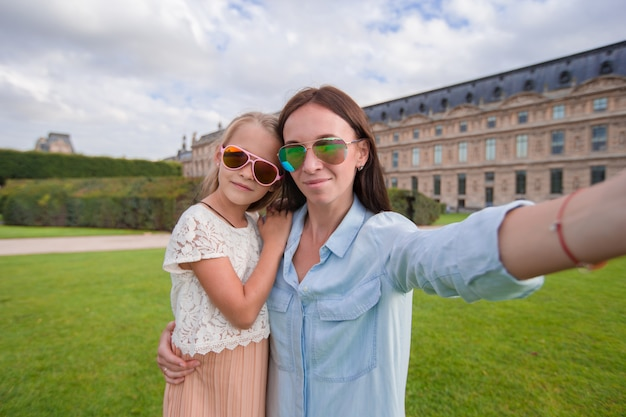 Happy mom and girl taking selfie in paris outdoors