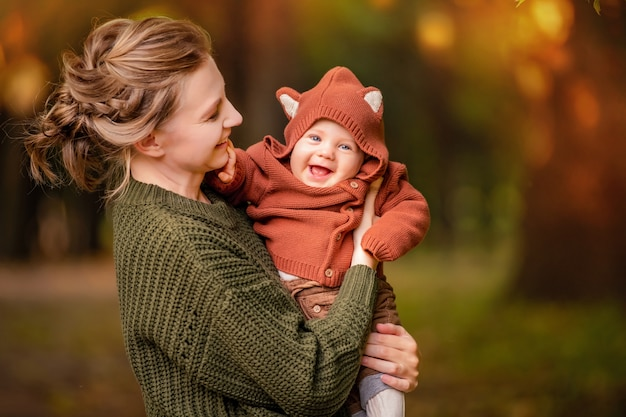 Happy mom holds a laughing baby in her arms