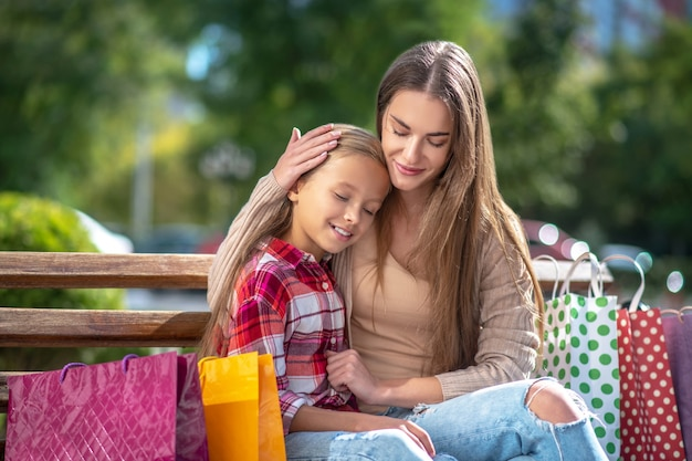Happy mom hugging her daughter on bench in the park