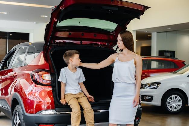 Счастливая мама обнимает сына после покупки новой машины в автосалоне
