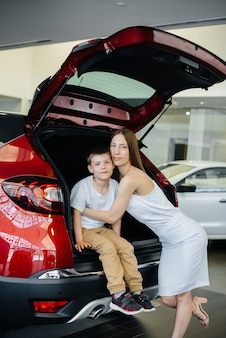 Happy mom hugs her son after buying a new car at a car dealership