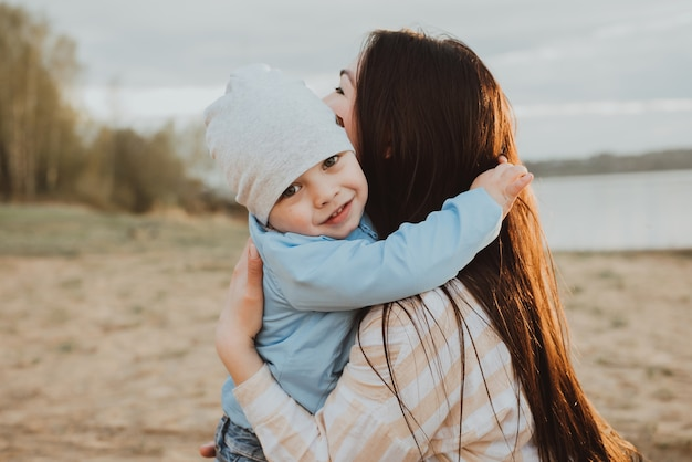 Happy mom hugs her son on the beach in summer in nature