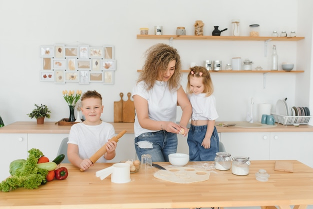 Happy mom and kids mixing ingredients for homemade cake, pie or cookie dough in the kitchen.