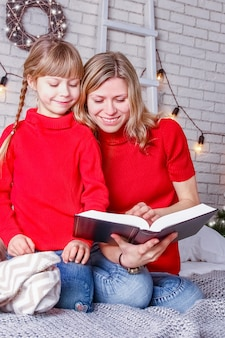 Happy mom and kids read book at home at christmas