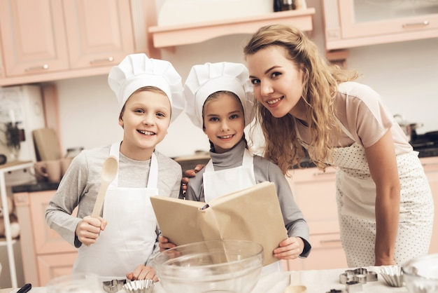 Happy mom and kids read recipe book at kitchen.