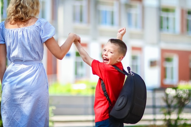 A happy mom leads the child to school on the way back to school