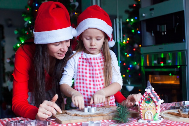 Happy mom and little girl in santa hat baking christmas gingerbread cookies together