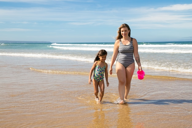 Happy mom and little girl wearing swimsuits, walking ankle deep in sea water on beach