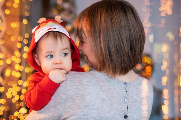 크리스마스 트리와 조명 화환 배경에 빨간 산타 순록 의상을 입고 아기와 함께 노는 행복한 엄마