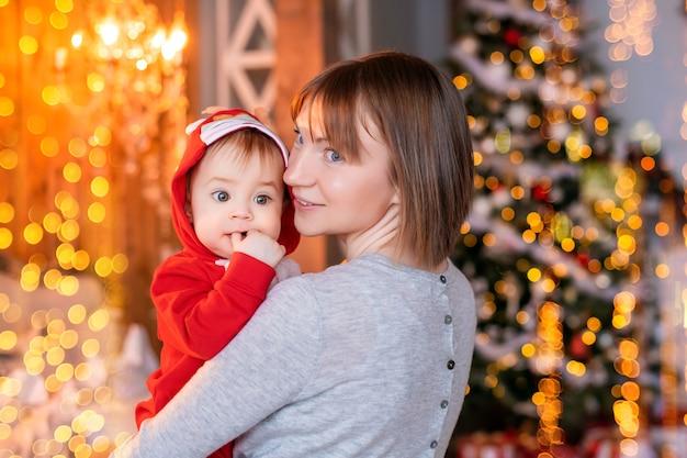 クリスマスツリーの背景に赤いサンタトナカイの衣装で彼女の幼児と遊ぶ幸せなお母さん
