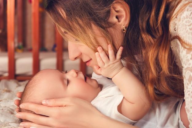 幸せなお母さんは彼女の幼い赤ちゃんの息子と遊ぶ