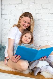 Счастливая мама читает веселую сказку в книге дочери и улыбается, сидя в гостиной
