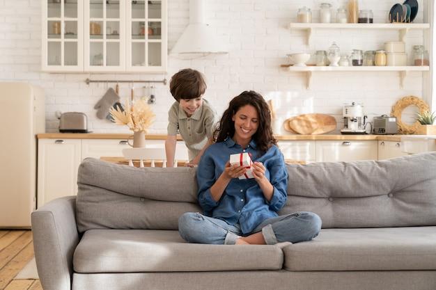 행복한 엄마는 어머니의 날에 돌보는 엄마에게 인사하는 미취학 아동을 사랑하는 손에 선물 상자를 들고 앉아 있습니다.