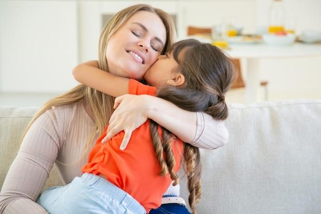 ソファの上の彼女の小さな女の子と一緒に座って、腕の中で子供を保持し、彼女を抱き締めて幸せなお母さん。