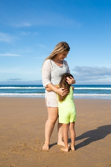Happy mom and sweet little daughter in summer clothes hugging while standing on ocean beach