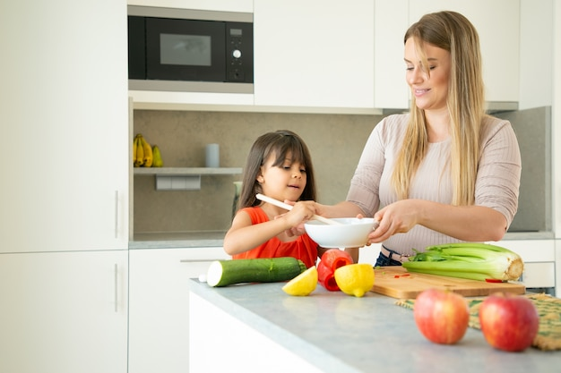野菜を料理するかわいい娘を教える幸せなお母さん。台所のカウンターでサラダをトスする母親を助ける少女。家族の料理のコンセプト