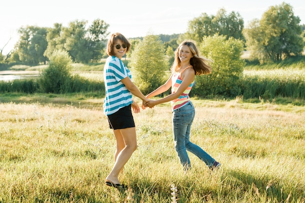 Happy mom and teen daughter smiling holding hands on nature