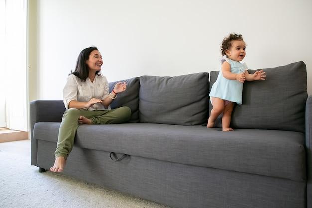 幸せなママはソファで彼女の最初の一歩を踏み出す女の赤ちゃんを見ています。全長。親子関係の概念