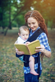 Happy mom with a baby in ergo backpack reading a fairy tale in the park.