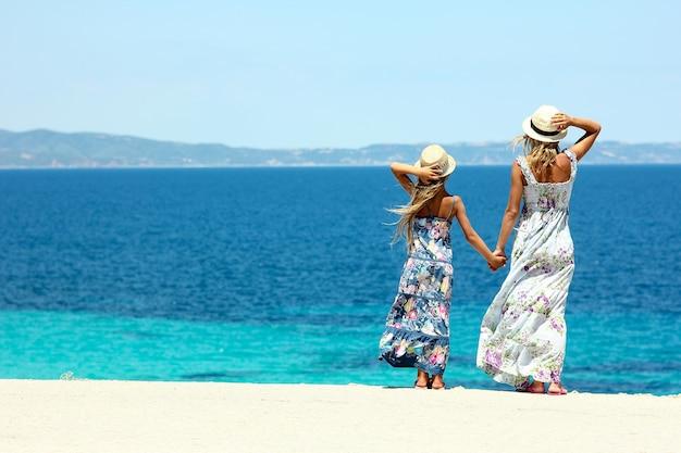 Счастливая мама с дочерью на берегу моря в шляпах и длинном платье