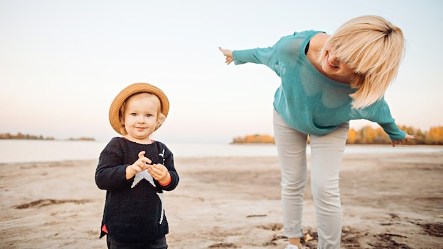 Happy mom with daughter have fun on the beach