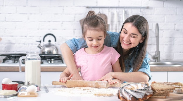 Happy mom with daughter preparing homemade cakes in a light kitchen close up.