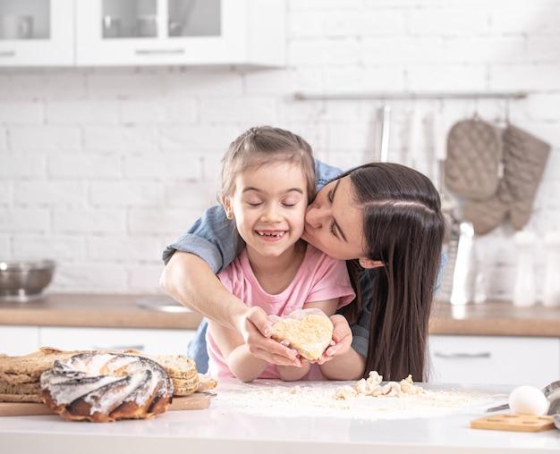 가벼운 부엌의 배경에 수제 케이크를 준비하는 딸과 함께 행복 한 엄마.