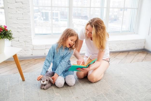 Счастливая мама с дочерью читают книгу и улыбаются, сидя на полу в гостиной